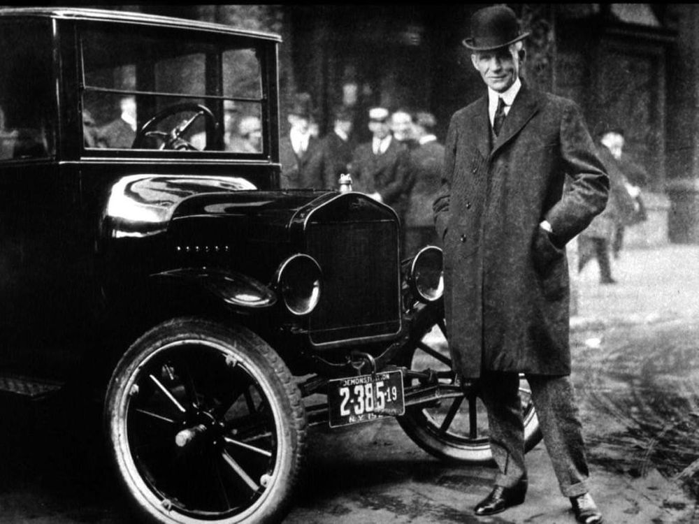 Henry Ford standing next to a Model T