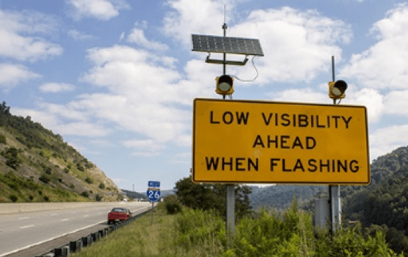 """A highway sign that reads, """"Low visibility ahead when flashing"""""""