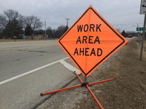 """A roadwork sign that reads, """"Work area ahead"""""""