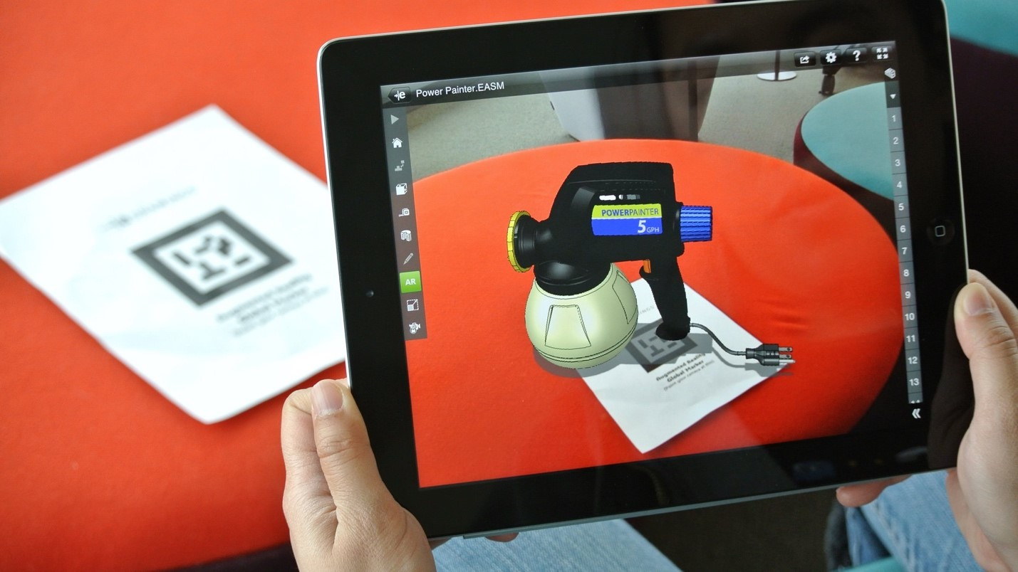 A representation of Marker-based AR with is iPad showing an image overlayed above an orange table and piece of paper.