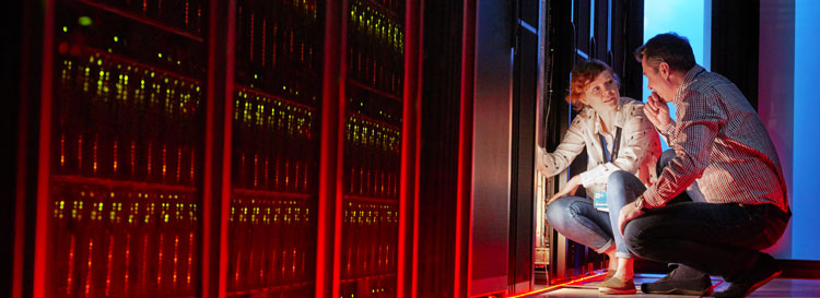 A man and a woman in a data center looking at racks