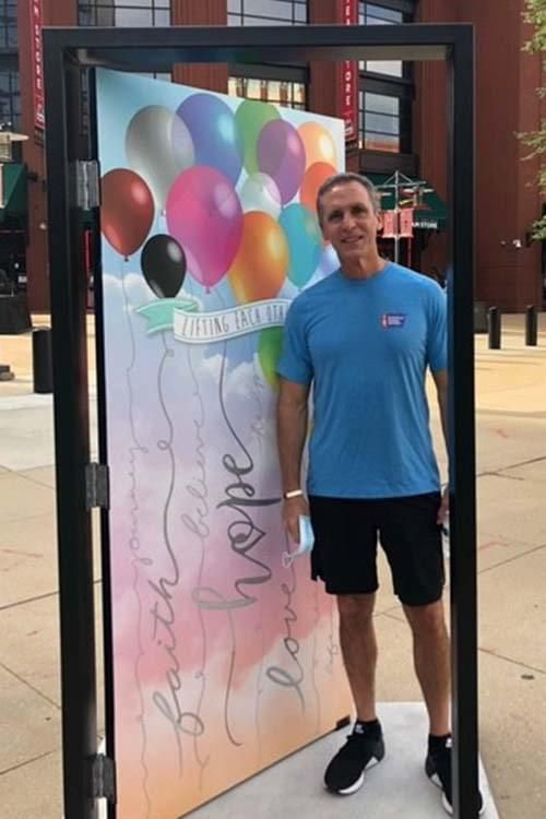 "WWT President Joe Koenig visits a 42 Doors of Hope installation in St. Louis. The door is decorated with colorful balloons and the words ""faith, love, hope."""