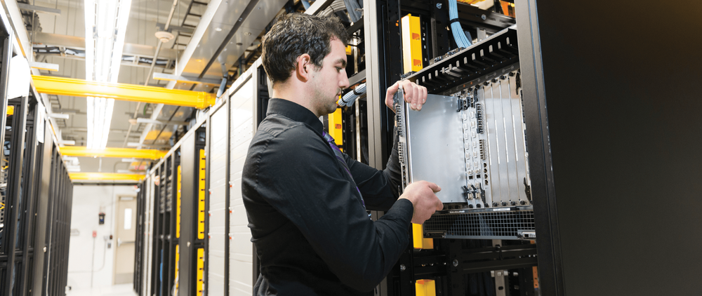 An engineer removing a server blade.