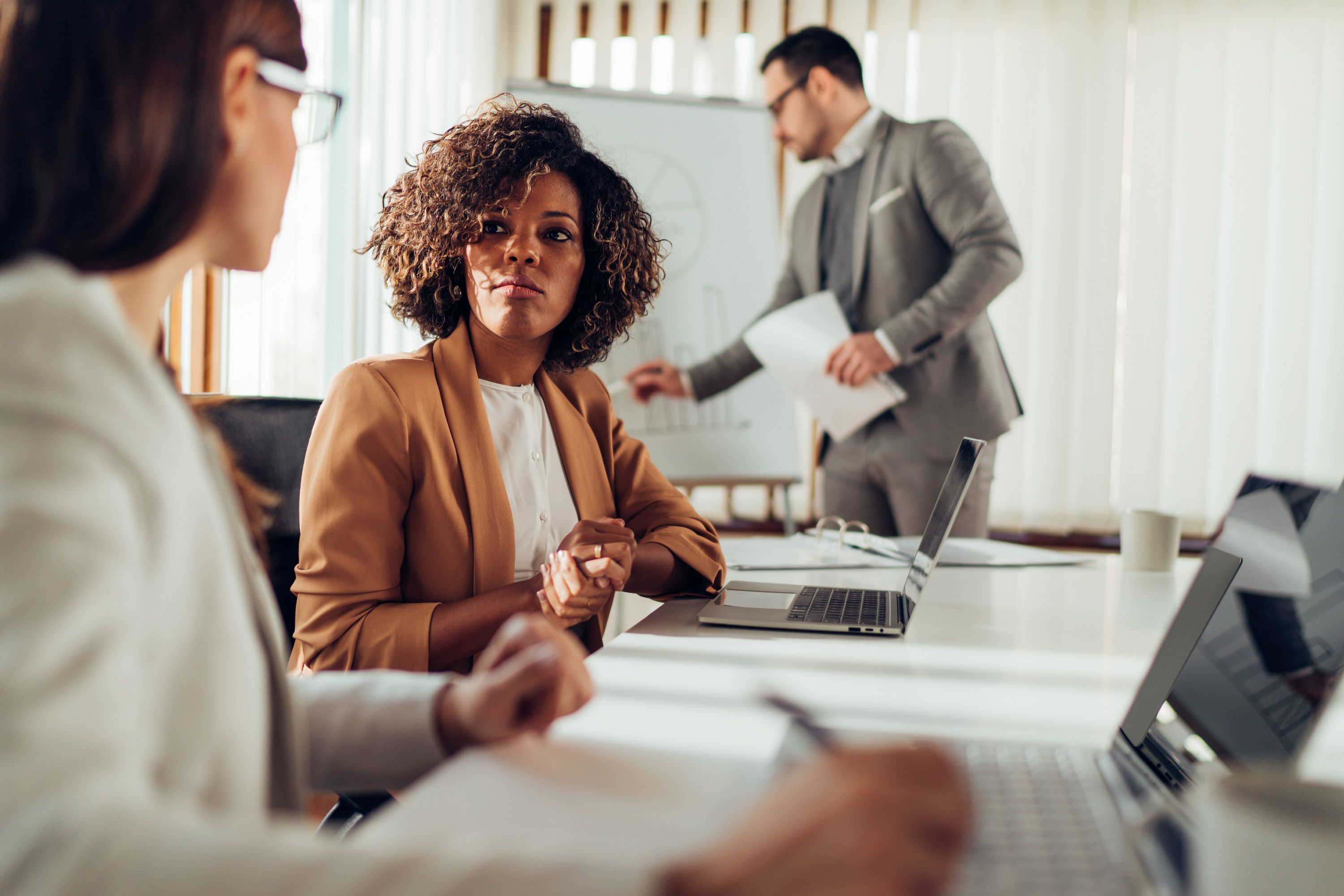Diverse business woman conversing with another business woman at a boardroom table while a business man writes on a whiteboard in the background