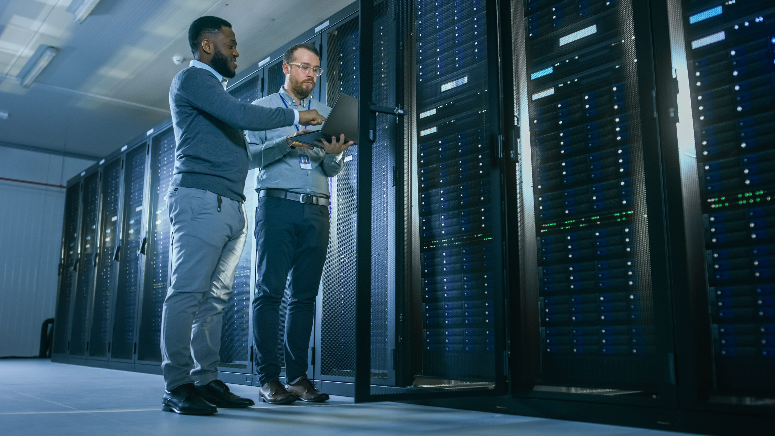Two diverse engineers standing in front of a row of servers looking at a computer.