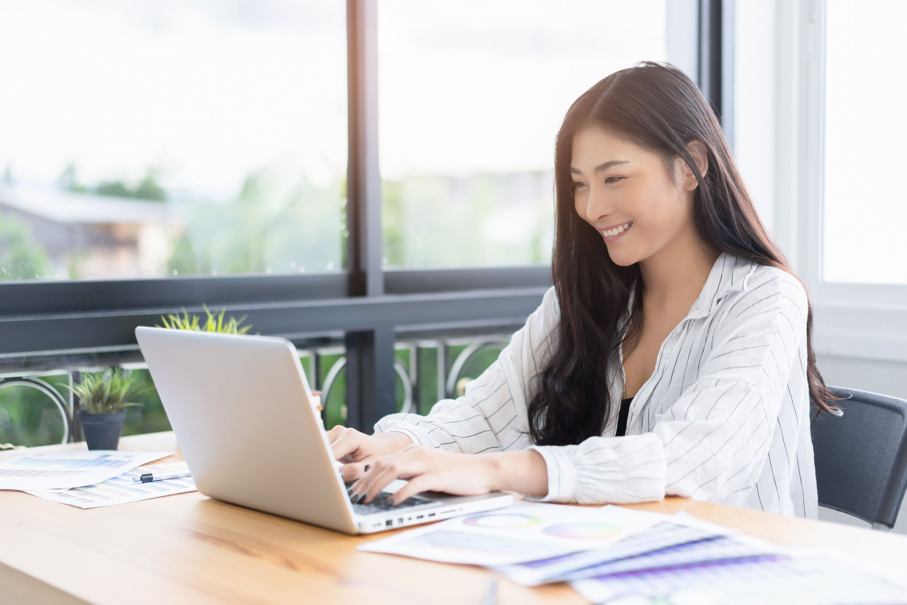 Diverse business woman smiling, sitting at a desk and typing on a laptop